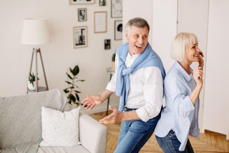 Spielendes, volles Paar, das zu Hause aktiv tanzt stockbild