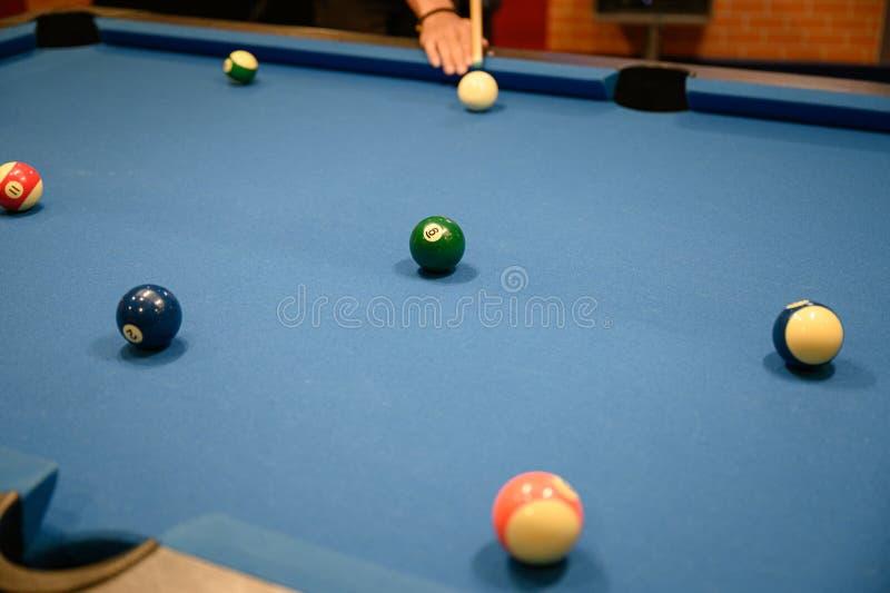 Spieler, der grünes Ballbillard auf Billardpool zielt stockfoto