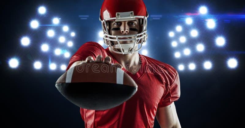 Spieler des amerikanischen Fußballs, der Ball gegen Scheinwerfer zeigt stockfoto