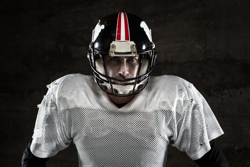 Spieler des amerikanischen Fußballs, der Kamera auf konkretem Hintergrund betrachtet lizenzfreie stockfotografie