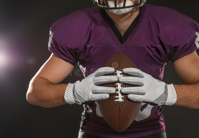 Spieler des amerikanischen Fußballs mit Ball auf dunklem Hintergrund stockbild