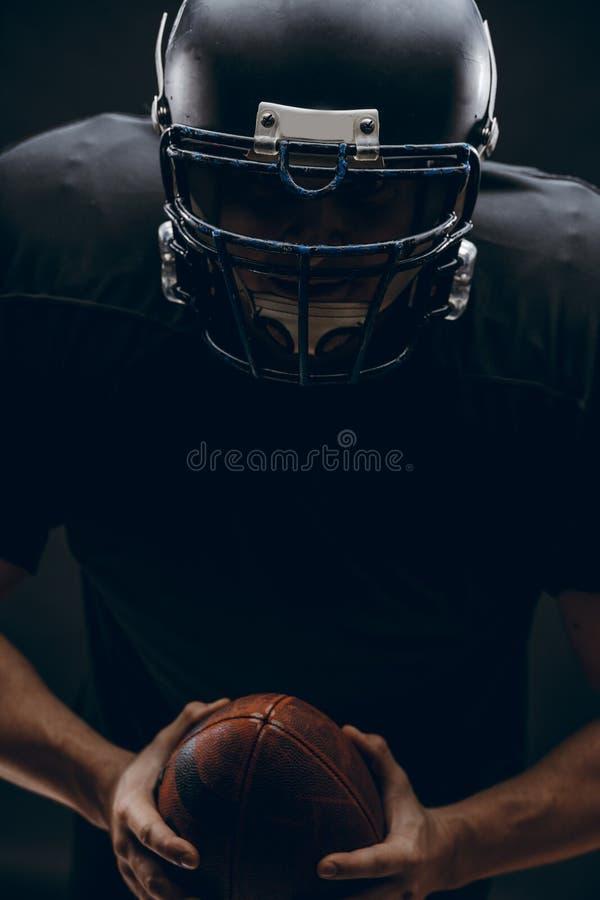 Spieler des amerikanischen Fußballs mit Sturzhelm und Rüstung mit einem Ball gegen schwarze Wand stockfoto