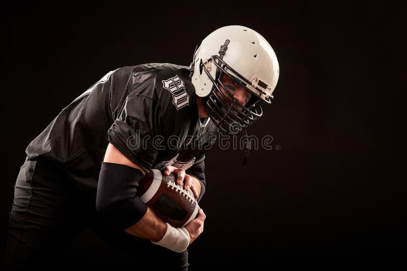 Spieler des amerikanischen Fußballs in der dunklen Uniform mit dem Ball bereitet vor sich, auf einem schwarzen Hintergrund anzugr stockfoto