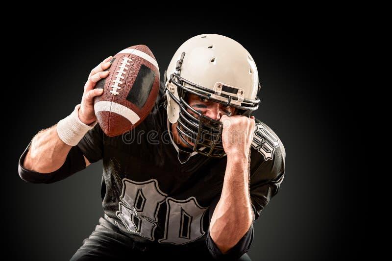 Spieler des amerikanischen Fußballs in der dunklen Uniform mit dem Ball bereitet vor sich, auf einem schwarzen Hintergrund anzugr stockfotografie