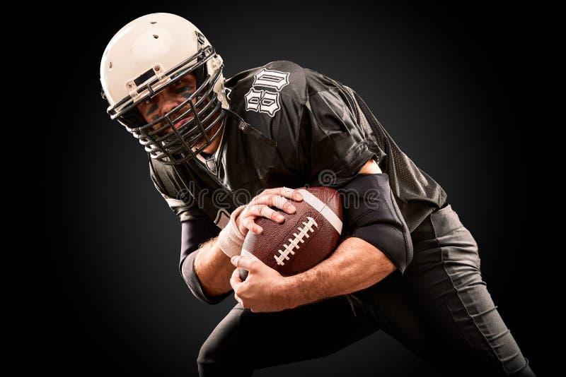 Spieler des amerikanischen Fußballs in der dunklen Uniform mit dem Ball bereitet vor sich, auf einem schwarzen Hintergrund anzugr lizenzfreies stockbild