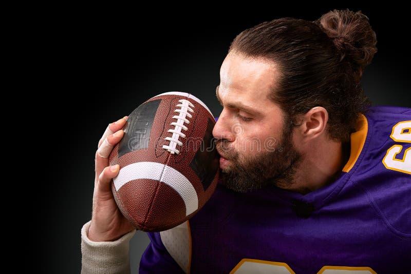 Spieler des amerikanischen Fußballs küsst den Ball lizenzfreies stockfoto
