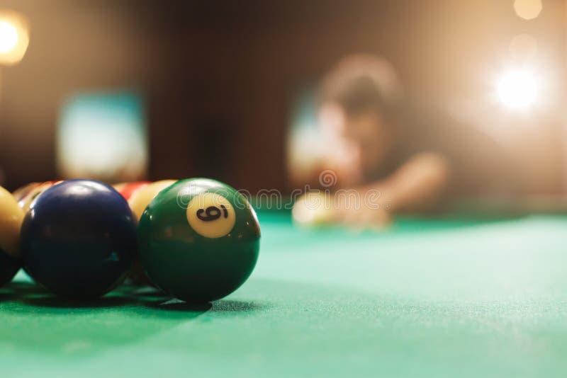 Spieler hat sich vorbereitet, die Bälle im Pool zu schlagen stockfotografie