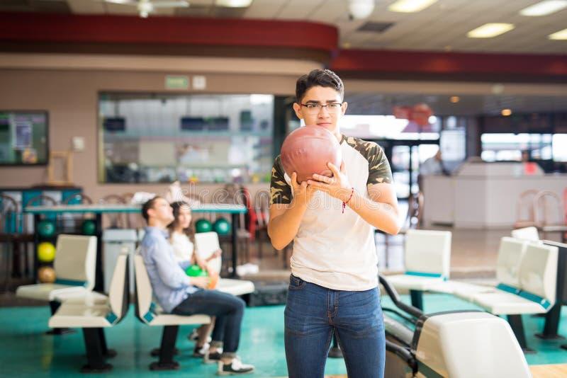 Spieler ungefähr, zum einer Bowlingkugel in der Gasse zu werfen stockfotografie