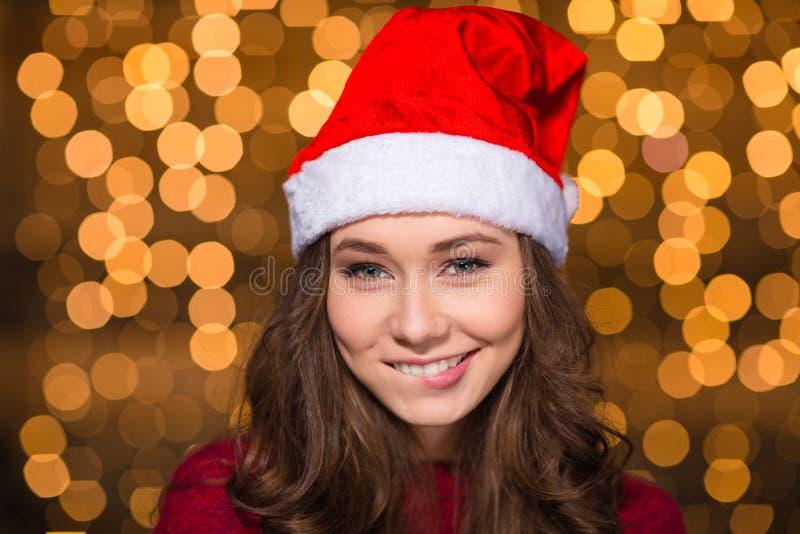 Spielerische attraktive junge Frau in Weihnachtsmann-Hut lizenzfreie stockfotos