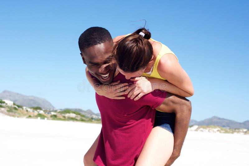Spielerische junge Paare, die draußen auf dem Strand lächeln lizenzfreie stockfotos