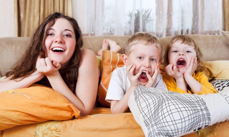 Spielerische Kinder im Morgenbett stockbild