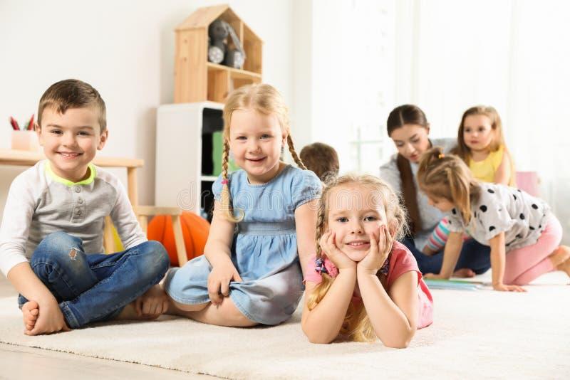 Spielerische kleine Kinder, die auf Boden stillstehen stockfoto