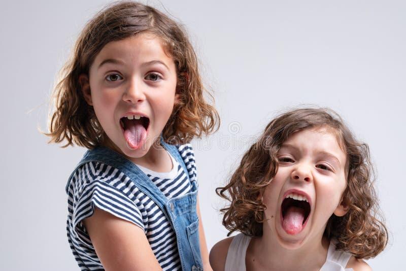 Spielerische kleine Mädchen, die heraus ihre Zungen haften stockfotografie
