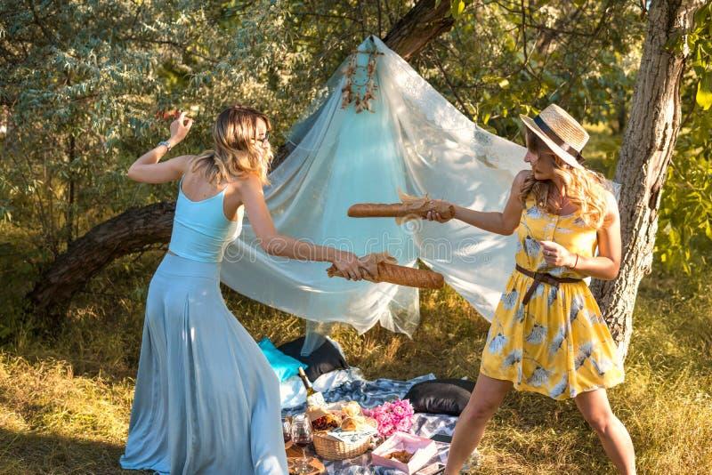 Spielerische Mädchen, die mit dem Brotstangenbrot macht Picknick kämpfen stockbild