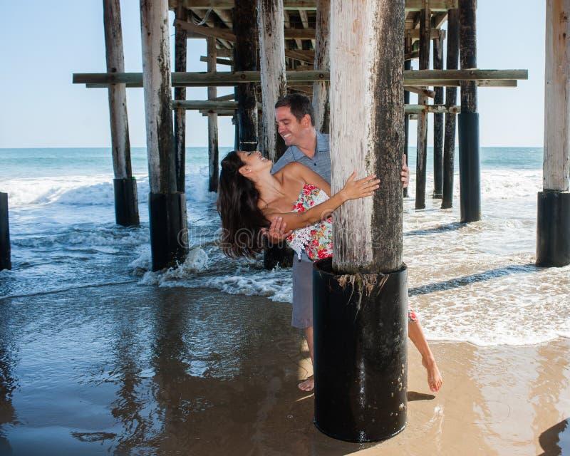 Spielerische Paare am Strand lizenzfreie stockbilder
