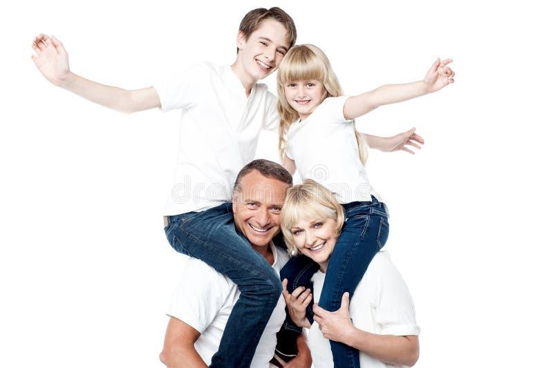 Spielerische vierköpfige Familie lokalisiert über Weiß stockfotos