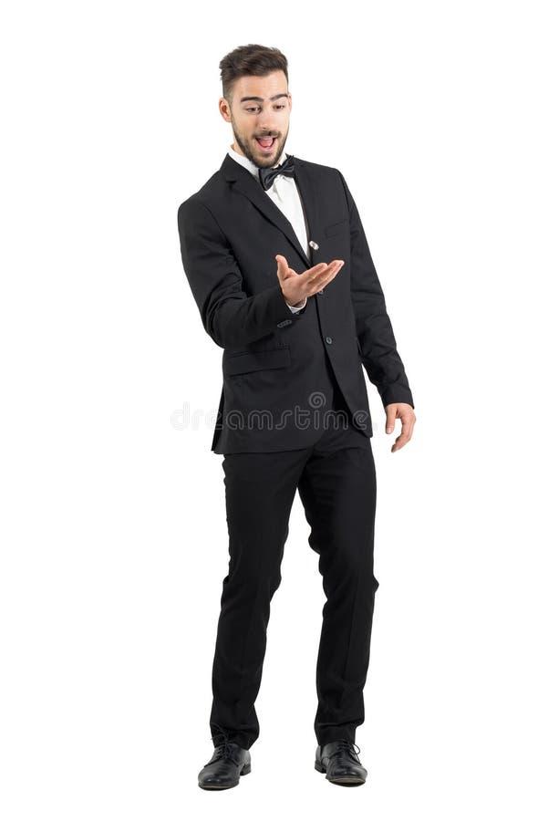 Spielerischer aufgeregter Jungebräutigam, der Ehering wirft stockbild