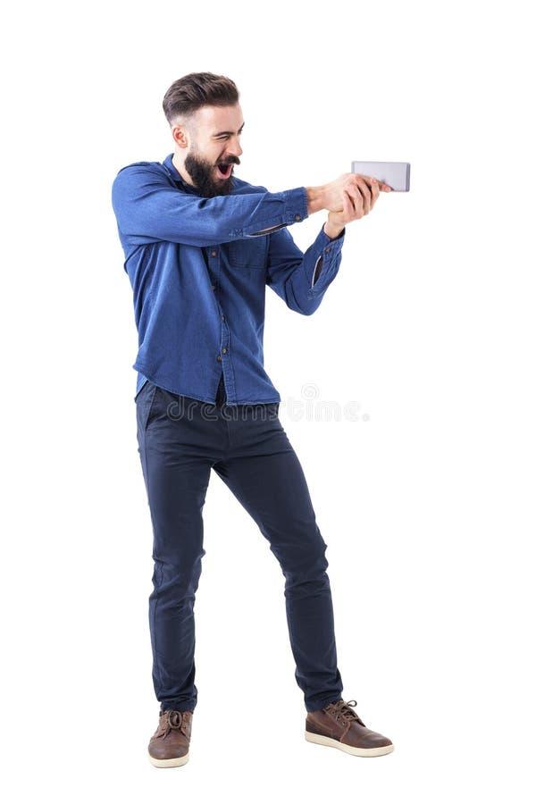 Spielerischer Geschäftsmann, der Handy als Pistole zielt als Actionfilmheld hält lizenzfreie stockfotos