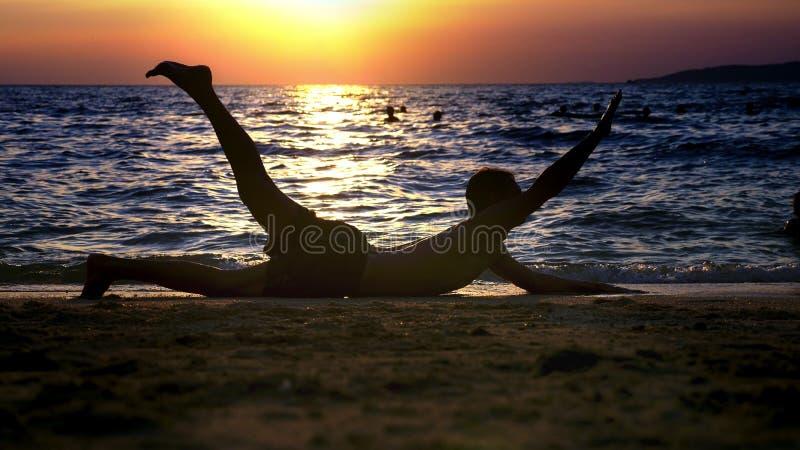 Spielerischer hübscher Kerl kurz gesagt Eignung, auf der Küste gegen den Hintergrund eines wunderbaren Sonnenuntergangs tuend lizenzfreies stockfoto