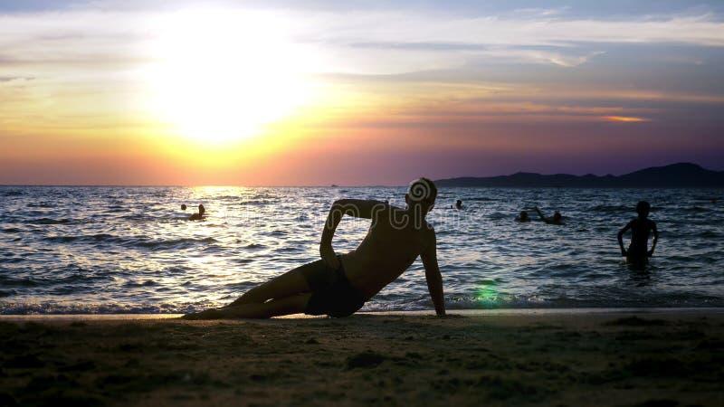 Spielerischer hübscher Kerl kurz gesagt Eignung, auf der Küste gegen den Hintergrund eines wunderbaren Sonnenuntergangs tuend lizenzfreie stockbilder