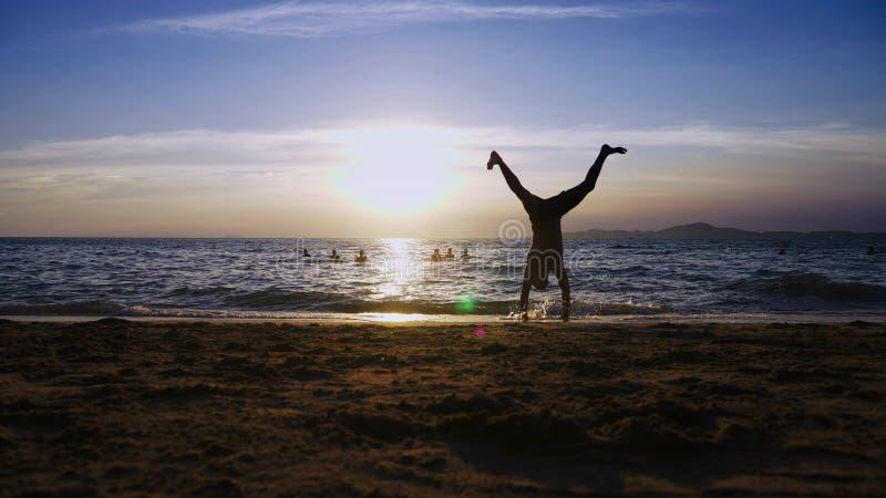 Spielerischer hübscher Kerl kurz gesagt Eignung, auf der Küste gegen den Hintergrund eines wunderbaren Sonnenuntergangs tuend stockfotos