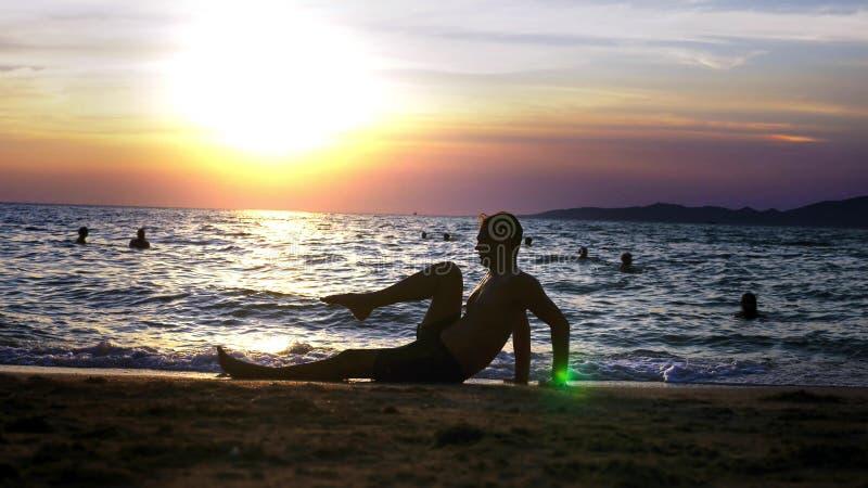 Spielerischer hübscher Kerl kurz gesagt Eignung, auf der Küste gegen den Hintergrund eines wunderbaren Sonnenuntergangs tuend lizenzfreies stockbild