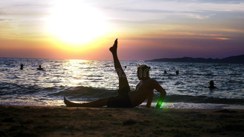 Spielerischer hübscher Kerl kurz gesagt Eignung, auf der Küste gegen den Hintergrund eines wunderbaren Sonnenuntergangs tuend lizenzfreie stockfotos