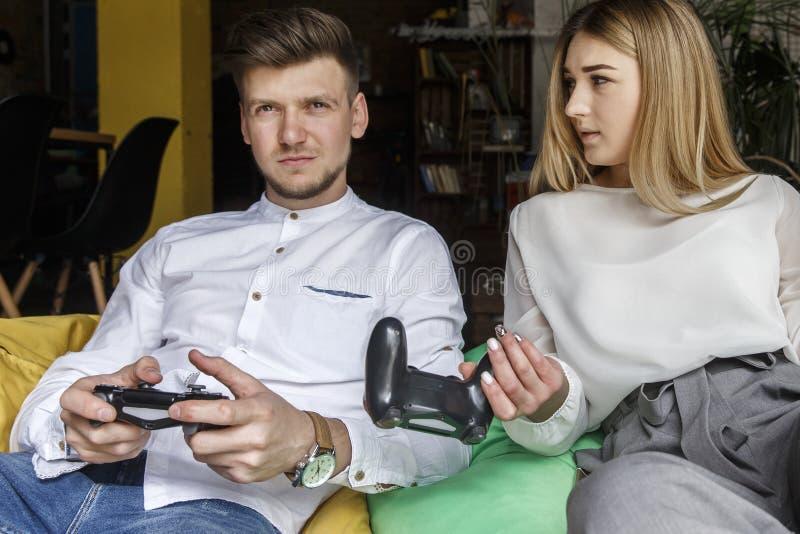 Spielerischer Mann und Frau sitzen zusammen auf weichen Stühlen Sie halten gamepads Kerl sitzt ruhig M?dchen betrachtet ihn stockbilder