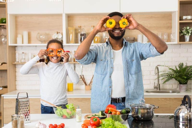 Spielerischer Vater und Tochter, die Spaß in der Küche hat lizenzfreies stockbild