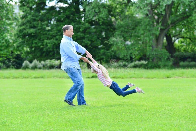 Spielerischer Vater und Tochter, die Spaß im Garten hat lizenzfreies stockfoto