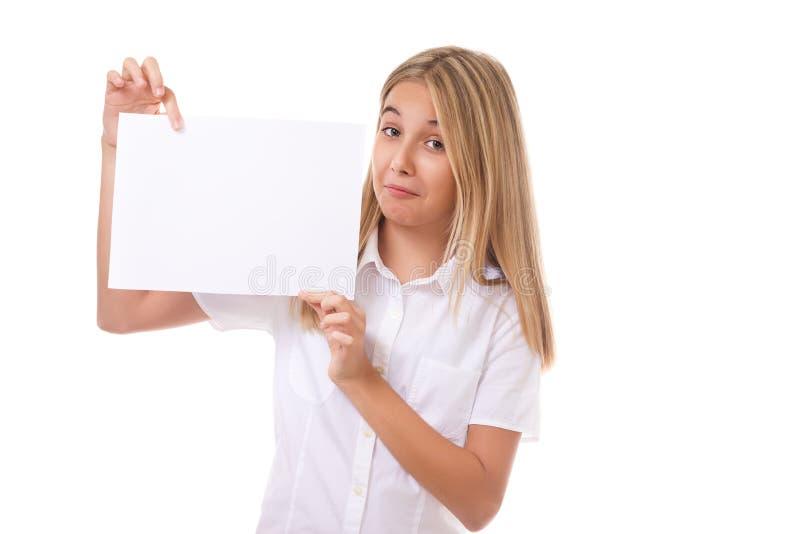 Spielerisches jugendlich Mädchen im weißen Hemd, das ein weißes Kommunikationsbrett, lokalisiert hält lizenzfreies stockfoto
