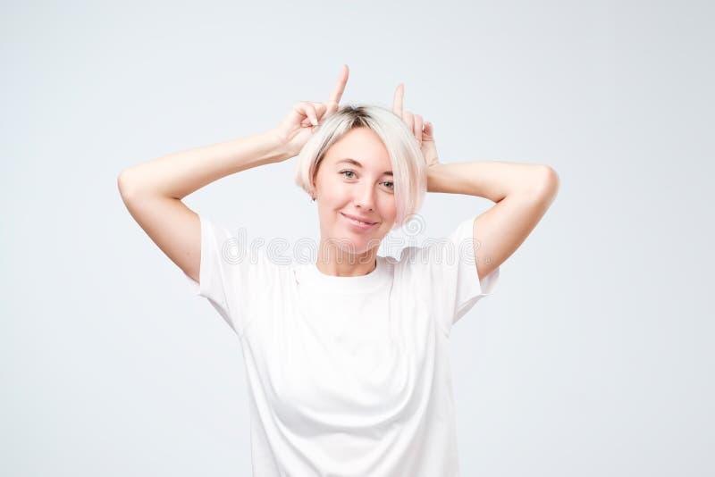 Spielerisches jugendlich Mädchen mit dem farbigen Frisurbehandlungsweißt-shirt, das Hörner zeigt lizenzfreies stockfoto