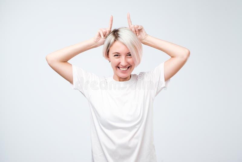 Spielerisches jugendlich Mädchen mit dem farbigen Frisurbehandlungsweißt-shirt, das Hörner zeigt stockfotografie