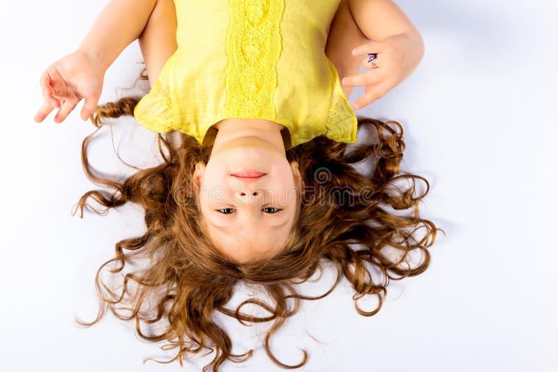 Spielerisches kleines Mädchen im gelben Kleid stockfoto