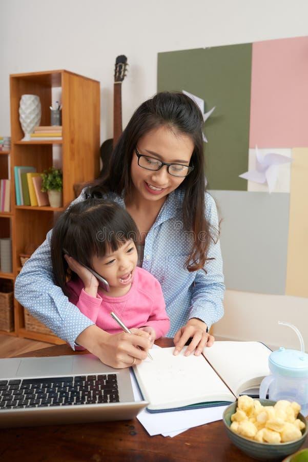 Spielerisches kleines Mädchen mit berufstätiger Mutter zu Hause lizenzfreie stockbilder