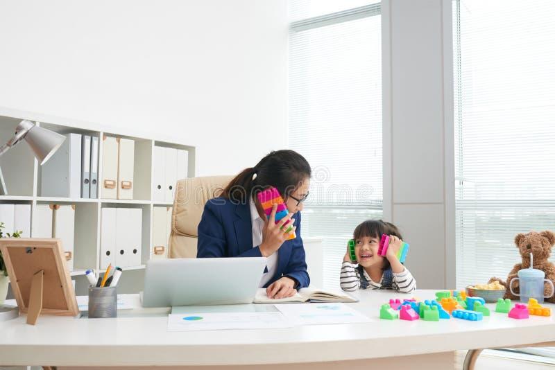 Spielerisches Mädchen mit berufstätiger Mutter im Büro lizenzfreie stockfotos