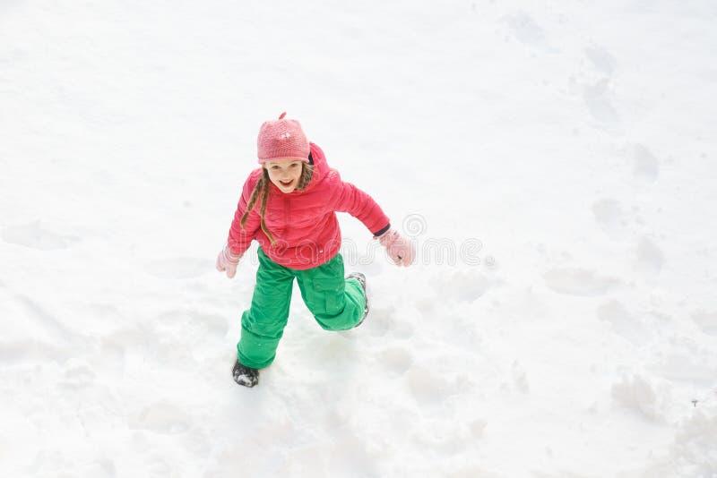 Spielerisches Mädchen mit den Borten, die in Schnee spielen und laufen lizenzfreies stockfoto