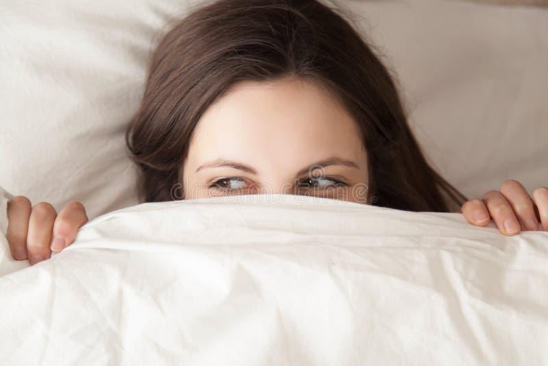 Spielerisches versteckendes Gesicht der jungen Frau unter der Decke, spähend vom duve stockfotos