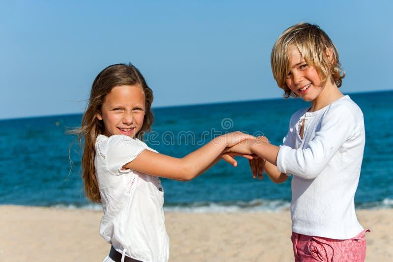 Spielhandspiel mit zwei Freunden auf Strand. stockbild