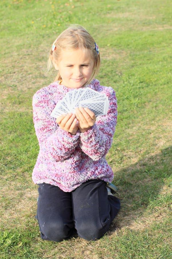 Spielkarten des kleinen Mädchens stockfotos