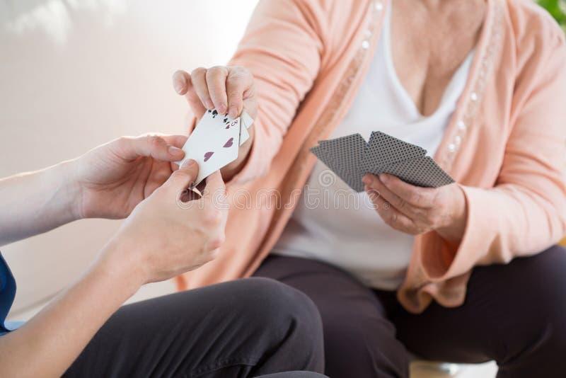 Spielkarten des Mannes mit älterer Frau lizenzfreie stockbilder