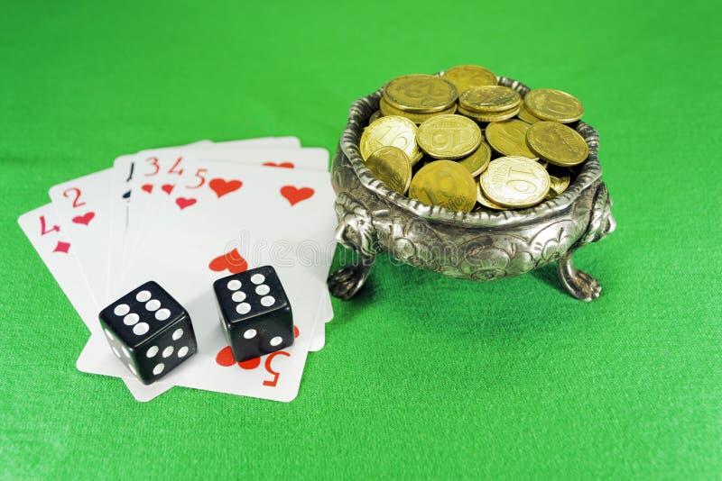 Spielkarten, Würfel und Schüssel auf drei Löwefuß lizenzfreie stockfotografie