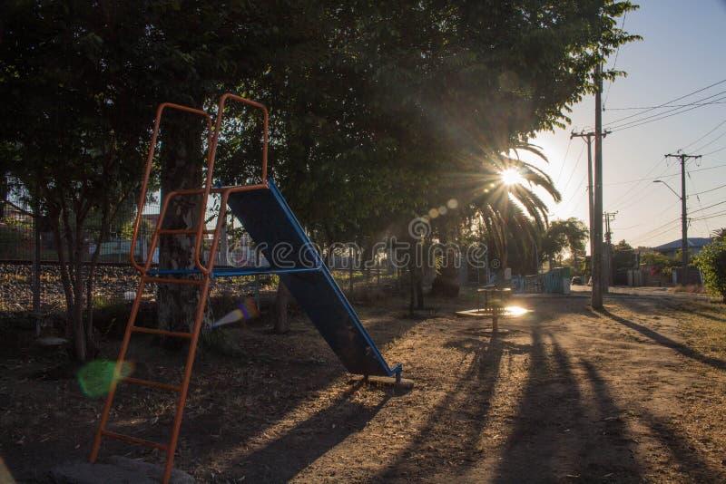 Spielplatz mit heller Filtration zwischen den Blättern einer Palme stockfoto