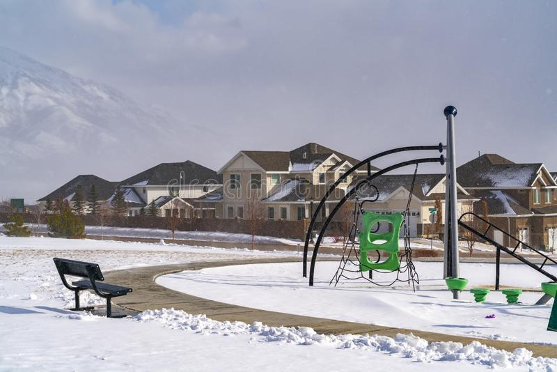 Spielplatz mit kletternden Rahmen gegen Häuser und schneebedeckter Berg im Winter lizenzfreie stockbilder
