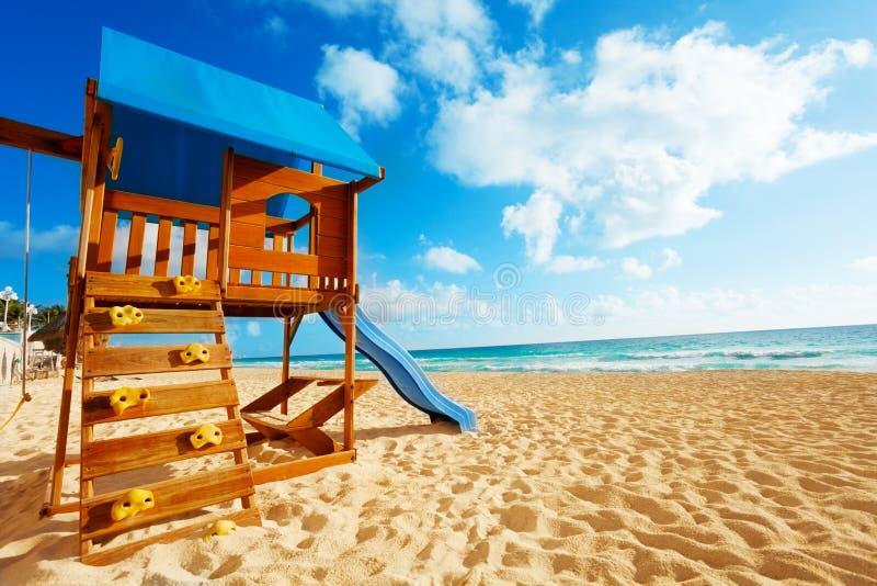 Spielplatzhaus auf dem Sandstrand nahe Meer lizenzfreie stockfotografie