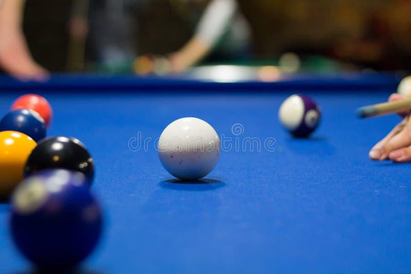 Spielspieler des Pools 8-ball zielt darauf ab, Bälle mit Stichwort zu schießen lizenzfreies stockfoto