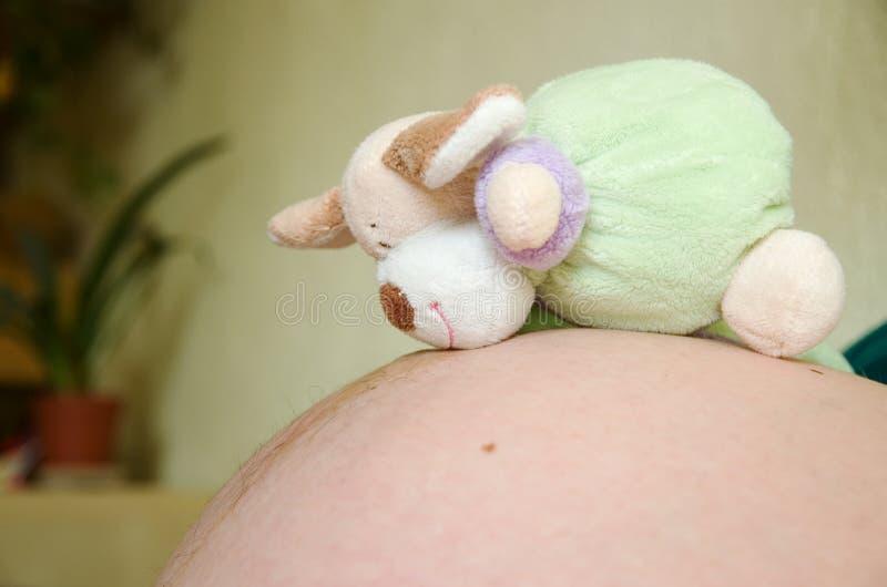 Spielzeug auf schwangerem Bauch stockbild
