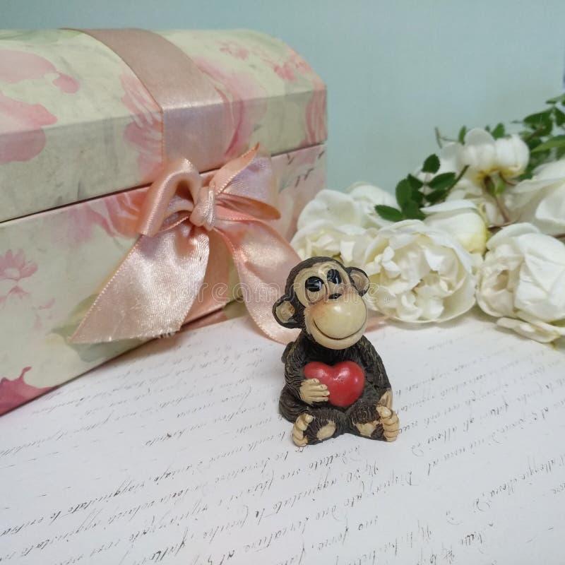 Spielzeugaffe mit rotem Herzen, weiße Rosen, Weinleseschmuckkästchen und Buchstabe stockfoto