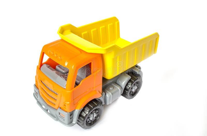 Spielzeugauto auf einem weißen lokalisierten Hintergrund LKW mit einem gelben Körper Frachtspielzeugauto lizenzfreies stockbild