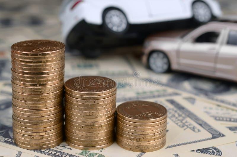 Spielzeugauto im Unfall auf einem Hintergrund von 100 Dollarscheinen und von Stapeln der goldenen Münzen stockfoto